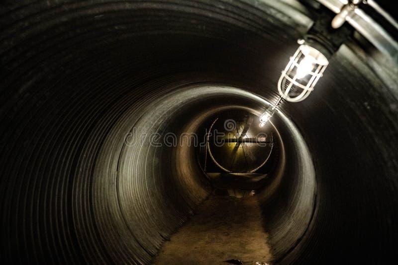 Ciemny podziemny stalowy tunel z elektrycznością zasilał linię latarki i ogromny fan w końcówce obrazy stock