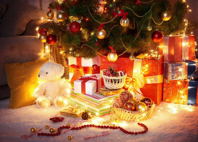 Ciemny pokój z iluminującą choinką, dekoracja i prezenty, domowy wnętrze przy nocą obraz stock