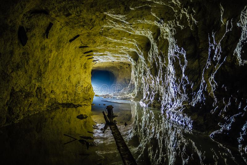 Ciemny przerażający brudny zalewający zaniechany kopalniany tunel fotografia royalty free