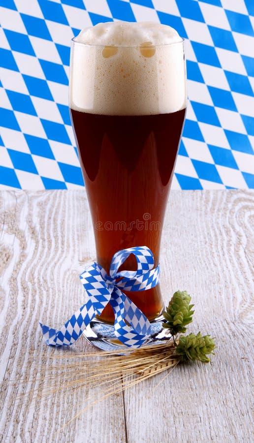 Ciemny pszeniczny piwo w szkle z błękitnym faborkiem na białym drewnianym tle zdjęcie stock