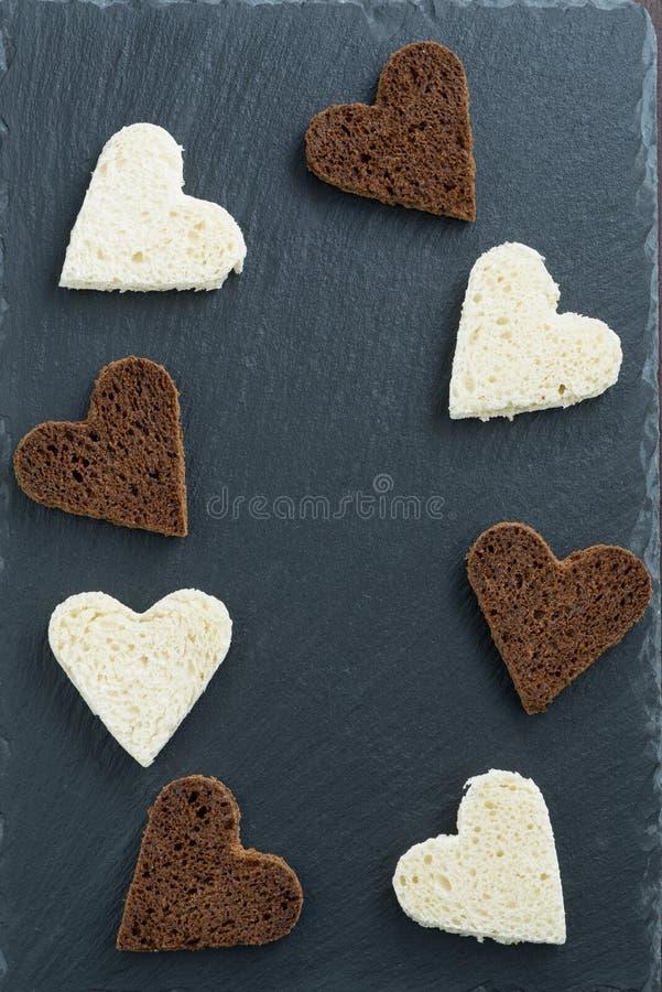 Ciemny tło z wznoszącym toast białym chlebem w kierowym kształcie i żytem fotografia royalty free