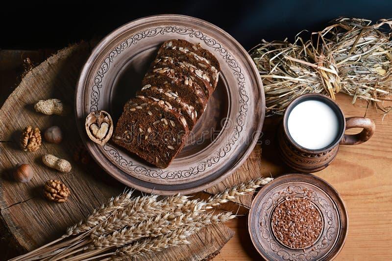 Ciemny zboże chleb z słonecznikowymi ziarnami, filiżanka mleko, dokrętki, lna ziarno, pszeniczni krótkopędy, pojęcie zdrowy łasow zdjęcie stock