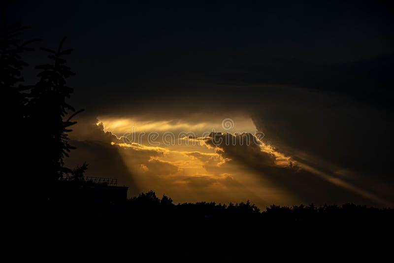 Ciemny zwarty niebo i promienie ciepły pomarańczowy światło dostaje z chmur zdjęcie royalty free