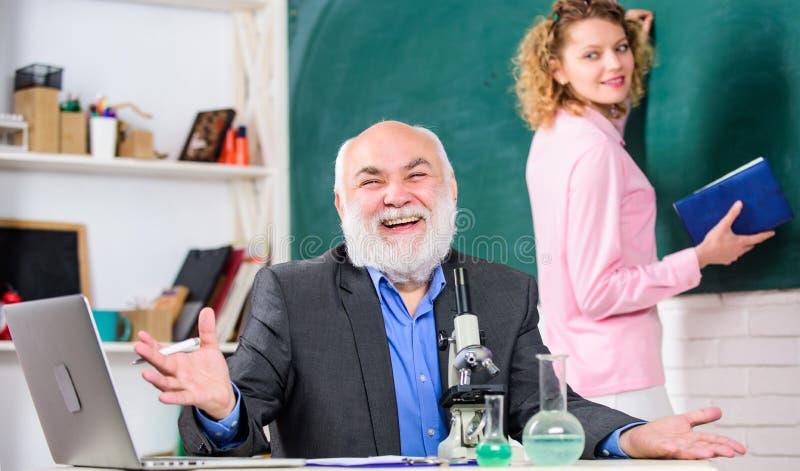 Ciencia de la biolog?a Biolog?a del estudio Investigaci?n biol?gica Profesor y muchacha con la libreta cerca de la pizarra Univer imagen de archivo
