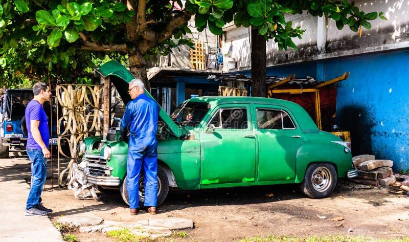 Cienfuegos, Куба - 2019 Механик исправляя старый классический американский автомобиль стоковое фото rf