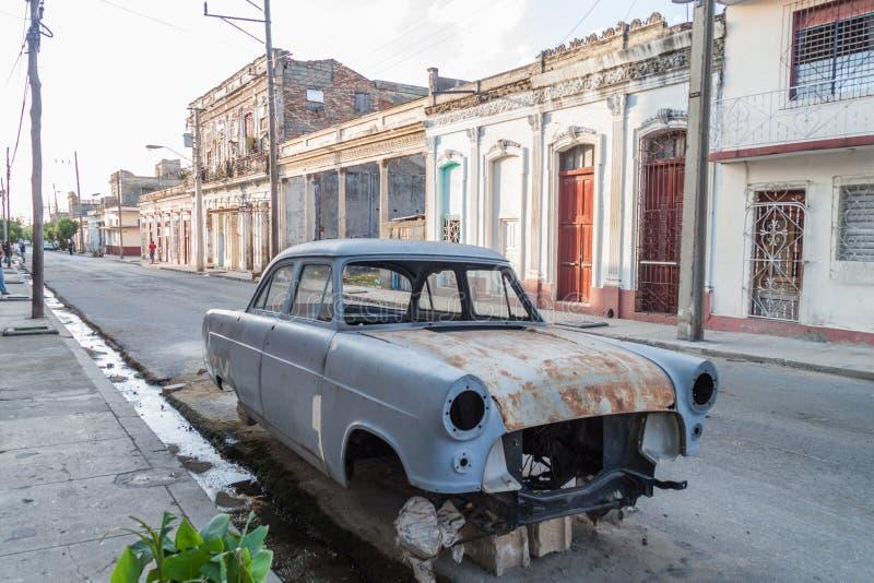 CIENFUEGOS, CUBA - 10 DE FEBRERO DE 2016: Vista de casas dilapidadas y de un coche en Cienfuegos, Cub fotografía de archivo libre de regalías