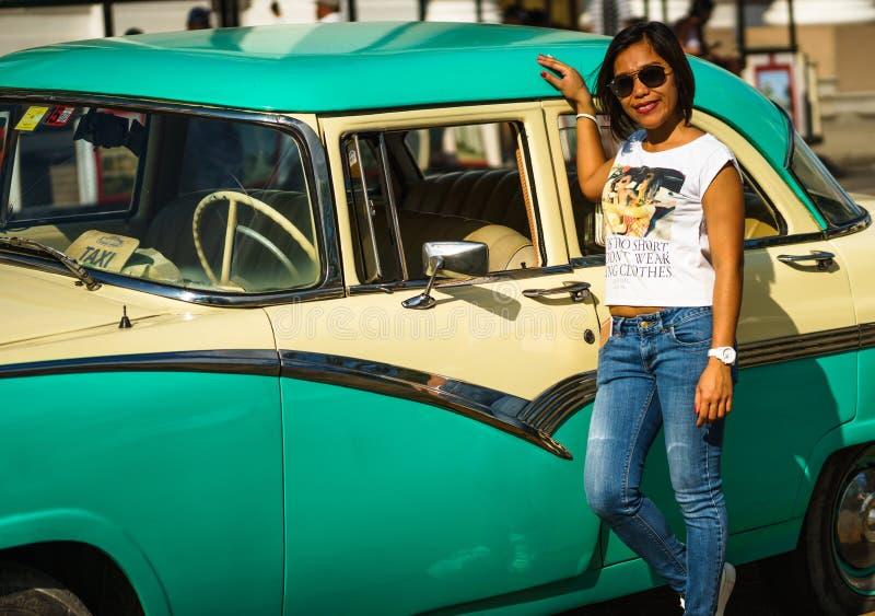 Cienfuegos, Cuba - 2019 Fille locale posant à côté d'une voiture américaine classique chez Cienfuegos Jose Marti Central Park Cie photographie stock