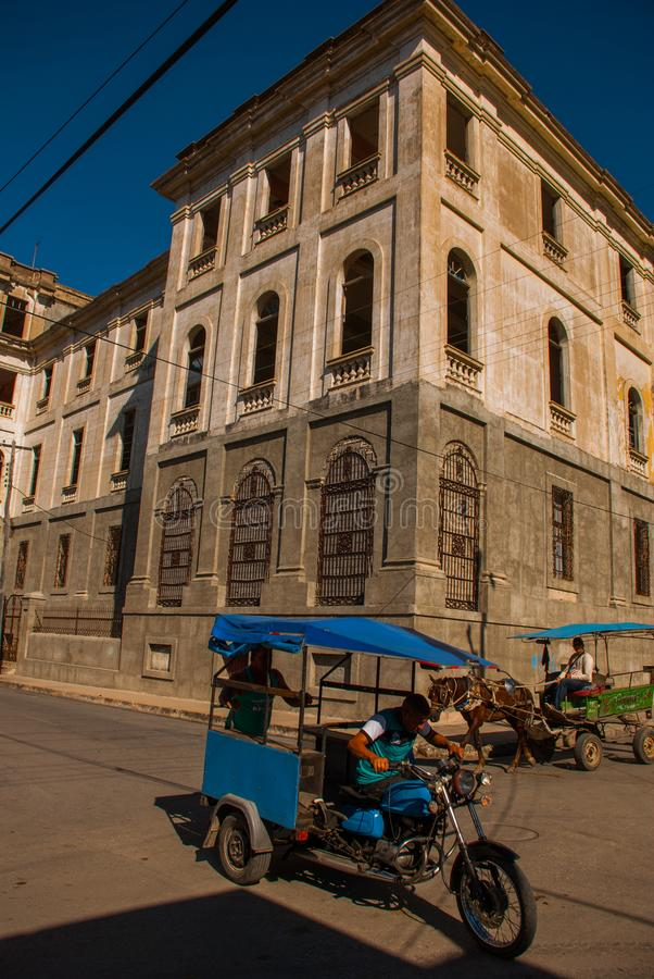 Cienfuegos Kuba: En vagn, en liten vagn med en häst och en motorcykel med en den chaufför tjänar som som en taxi royaltyfri fotografi