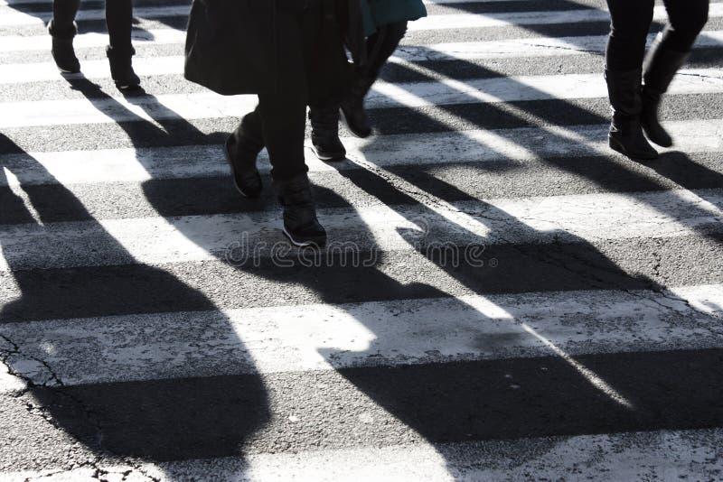Cienie i sylwetki ludzie krzyżuje ulicę obraz stock