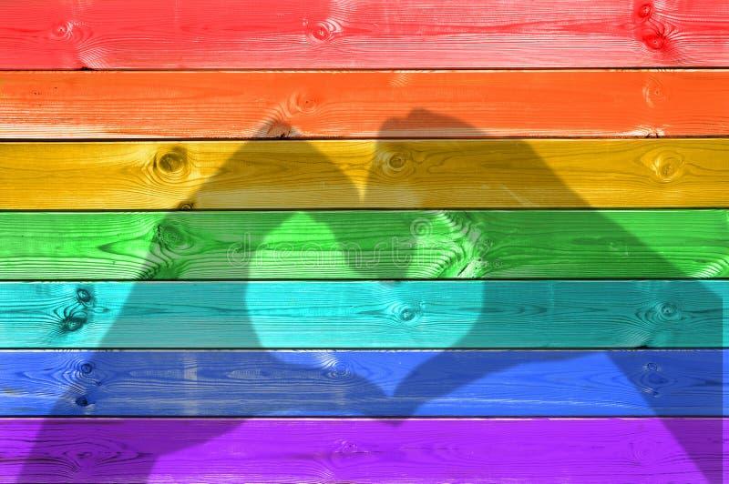 Cienie ręki tworzy serce na kolorowa tęcza malującym drewnie zaszalują tło, homoseksualista flaga miłości pojęcie fotografia stock