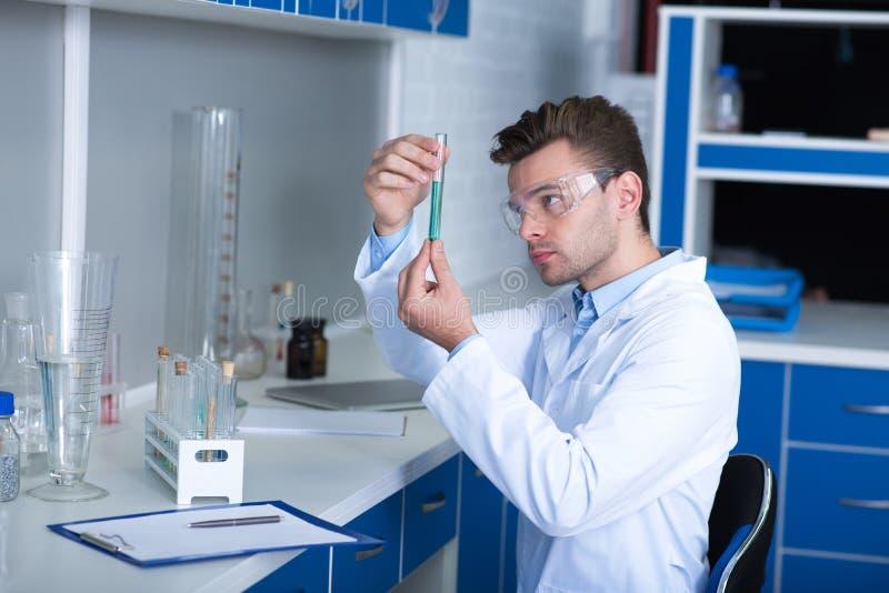 Científico agradable adulto que pasa por alto el frasco y que conduce la investigación imagenes de archivo