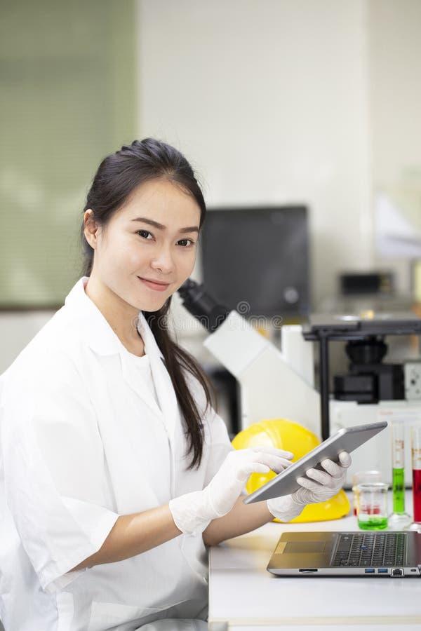 Científico asiático de la biotecnología de la mujer que hace la prueba química del microscopio en laboratorio foto de archivo