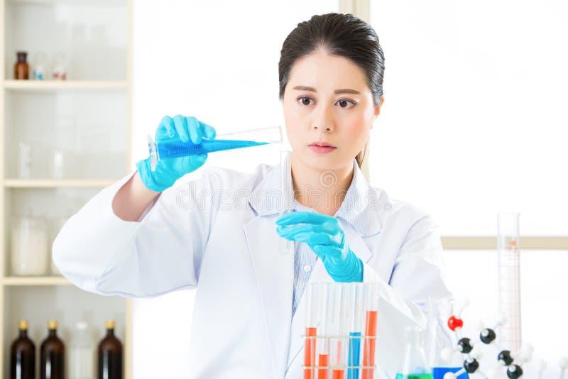 Científico asiático joven que mide con una pipeta en laboratorio de ciencias de la vida imagen de archivo