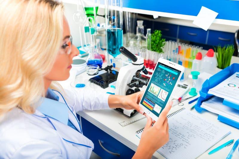 Científico atractivo joven de la mujer que usa la tableta en el la foto de archivo