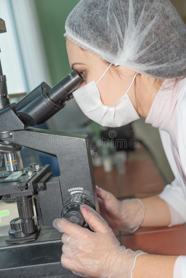 Científico de la mujer que mira en un microscopio imágenes de archivo libres de regalías