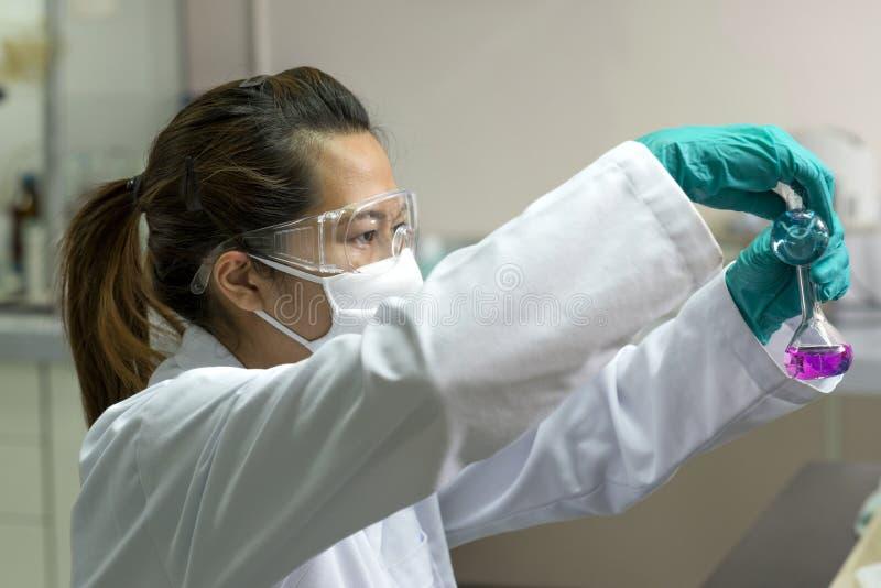 Científico de la señora que aclara las sustancias químicas en el vidrio de la prueba imagenes de archivo
