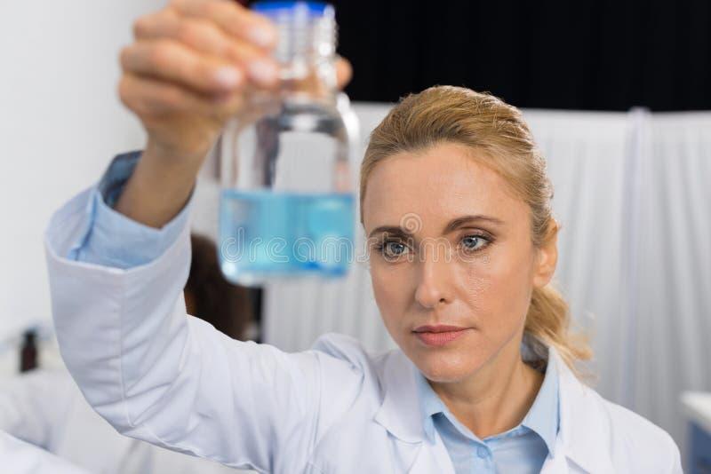 Científico de sexo femenino Examine Flask With Luquid azul que trabaja en el laboratorio moderno, investigador atractivo Making d fotos de archivo