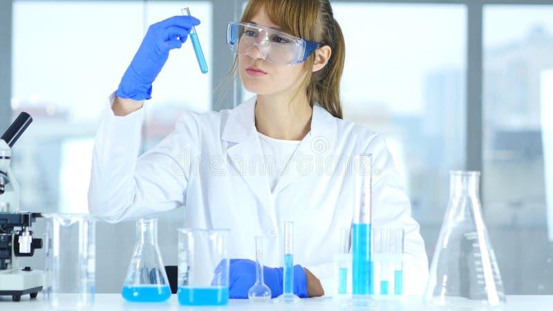 Científico de sexo femenino de la investigación que mira la solución azul en tubo de ensayo en laboratorio fotos de archivo libres de regalías