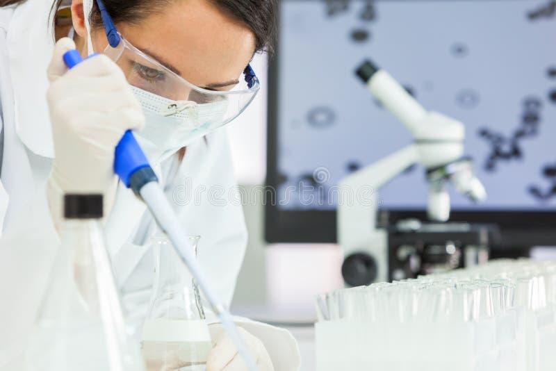Científico de sexo femenino With Pipette de la investigación y frasco en laboratorio fotografía de archivo libre de regalías
