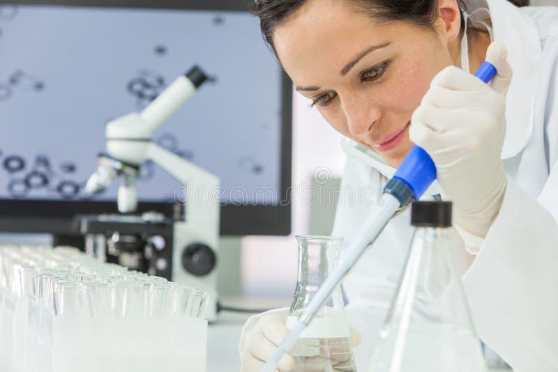 Científico de sexo femenino With Pipette de la investigación y frasco en laboratorio imagenes de archivo