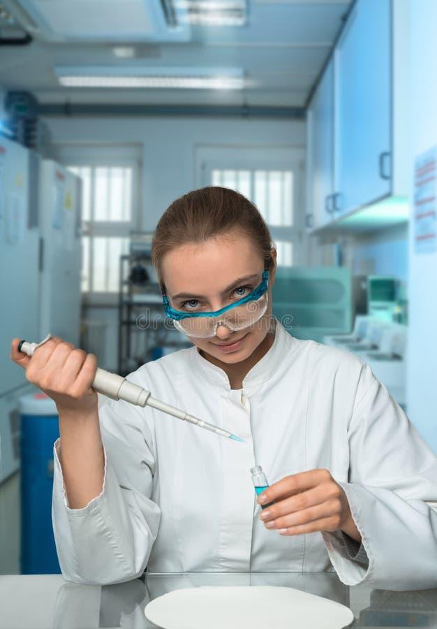 Científico de sexo femenino que mide con una pipeta la muestra en laboratorio moderno fotos de archivo libres de regalías