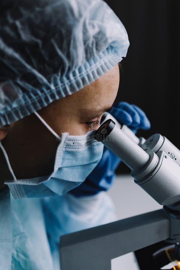 Científico de sexo femenino que mira el microscopio foto de archivo libre de regalías