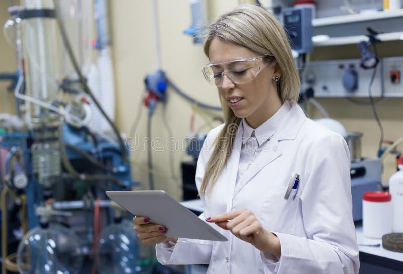 Científico de sexo femenino que usa la tableta en el laboratorio imagenes de archivo