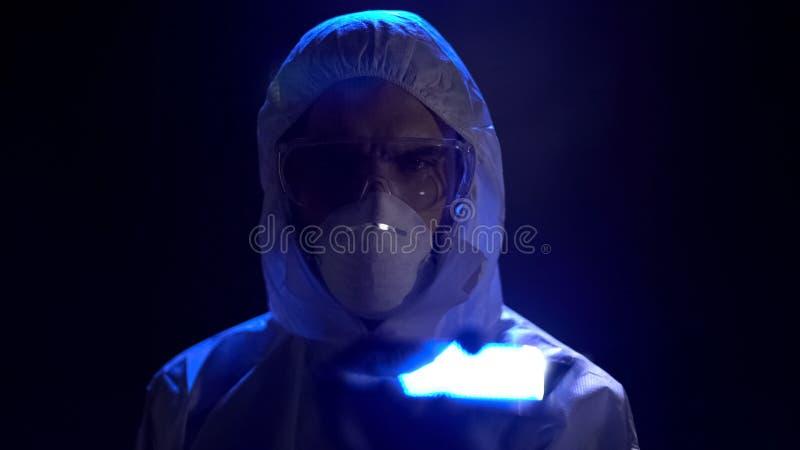 Científico de sexo masculino en máscara protectora y gafas en el fondo oscuro, profesión fotografía de archivo