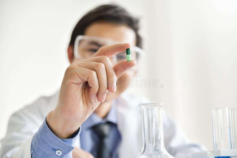 Científico de sexo masculino joven que sostiene una píldora imágenes de archivo libres de regalías