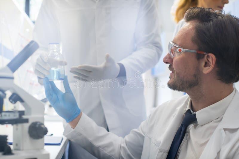 Científico de sexo masculino Working With Microscope, Team In Laboratory Doing Research, hombre y mujer haciendo experimentos cie foto de archivo