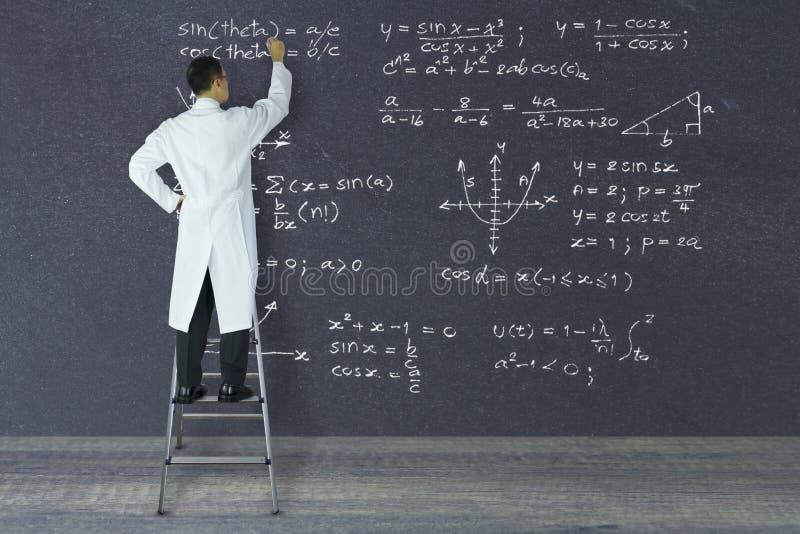 Científico del genio que escribe fórmulas matemáticas imagenes de archivo