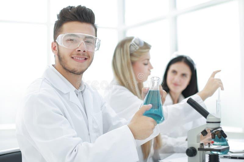 Científico del hombre que sostiene un frasco de líquido para el experimento foto de archivo libre de regalías