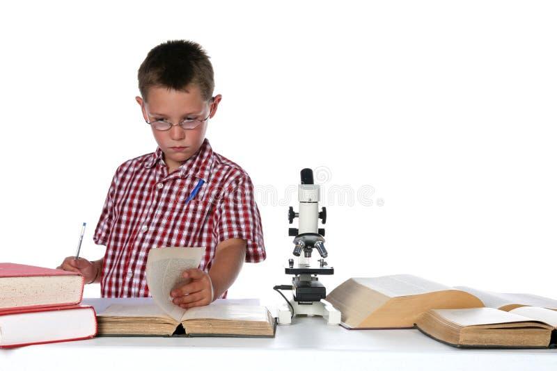 Científico del niño en vidrios que consulta sus libros imágenes de archivo libres de regalías