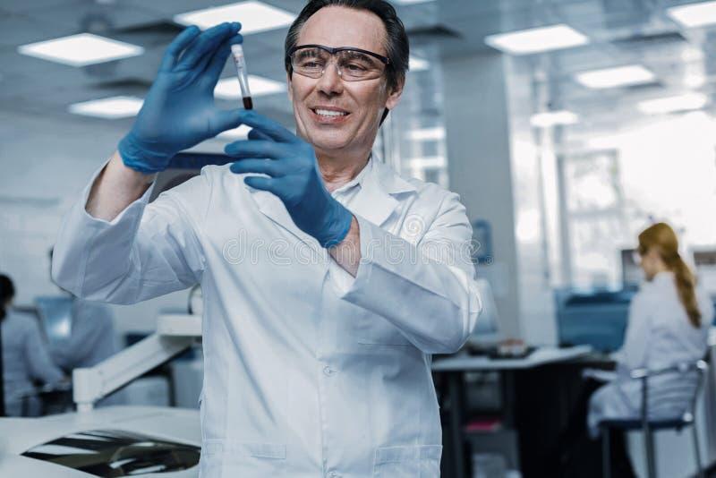 Científico elegante del genio que mira la vacuna fotos de archivo