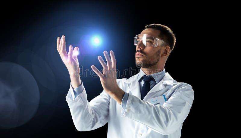 Científico en capa del laboratorio y gafas con la luz imágenes de archivo libres de regalías