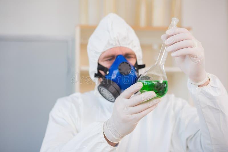 Científico en traje protector que examina el precipitado verde foto de archivo