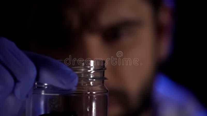 Científico forense que sostiene el tarro de cristal en manos, pruebas de examen de la escena del crimen imágenes de archivo libres de regalías