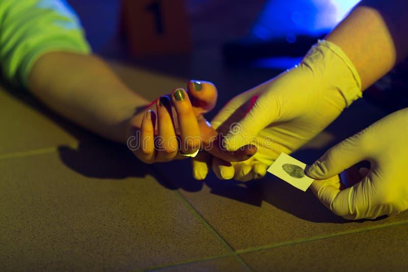 Científico forense que toma la huella dactilar foto de archivo