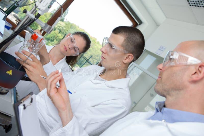 Científico joven del estudiante del phd que mira a través del microscopio fotografía de archivo libre de regalías