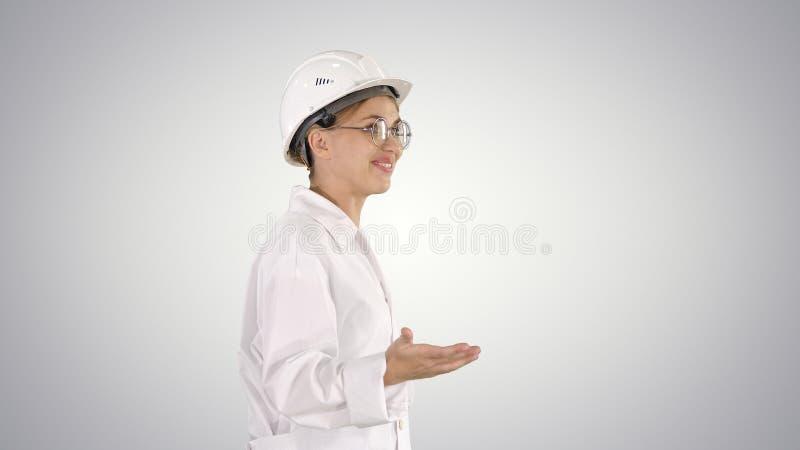 Científico joven en capa y el casco de protección del laboratorio que camina y que dice algo en fondo de la pendiente foto de archivo
