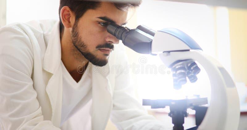 Científico joven que mira a través del microscopio en laboratorio fotos de archivo libres de regalías