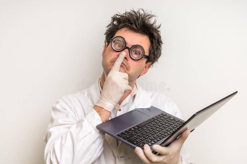 Científico loco con el ordenador portátil que trabaja en su laboratorio fotos de archivo