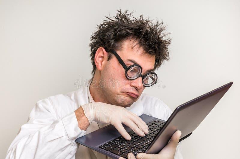 Científico loco con el ordenador portátil que trabaja en su laboratorio foto de archivo
