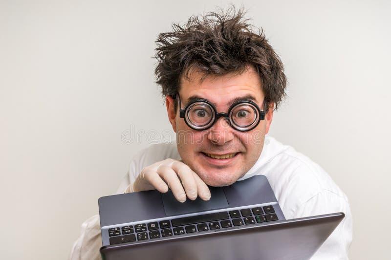 Científico loco con el ordenador portátil que trabaja en su laboratorio fotos de archivo libres de regalías