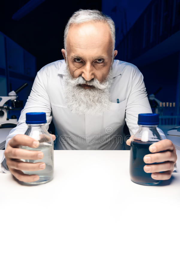 Científico malvado con las botellas con los reactivo que miran la cámara el lugar de trabajo foto de archivo libre de regalías