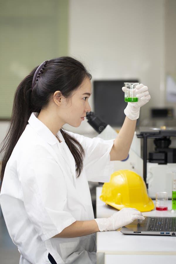 Científico o ingeniero asiático de la mujer que trabaja en prueba química de la investigación en laboratorio foto de archivo