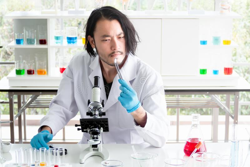 Científico o químico asiático que mira una tableta en laboratorio, la medicina de prueba del hombre joven en el experimento médic imagen de archivo