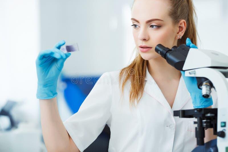 Científico que analiza la diapositiva del microscopio en el laboratorio Trabajo femenino en laboratorio con el microscopio Examen foto de archivo