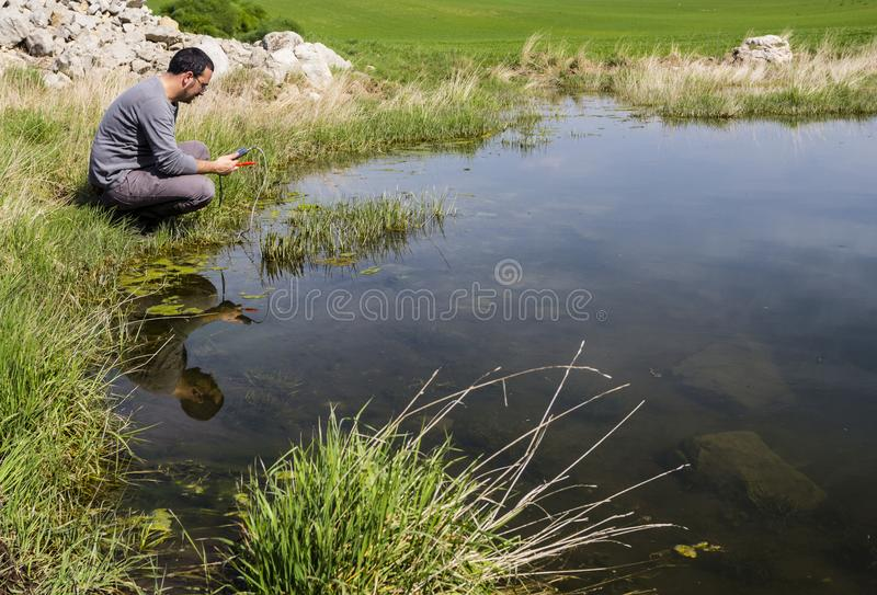 Científico que mide calidad del agua ambiental en un humedal imágenes de archivo libres de regalías