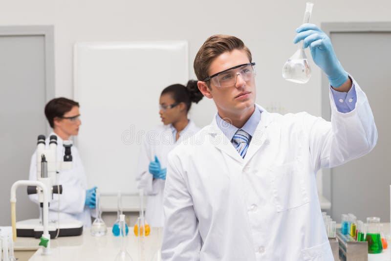 Científico que mira el precipitado blanco mientras que colegas que hablan junto fotografía de archivo libre de regalías